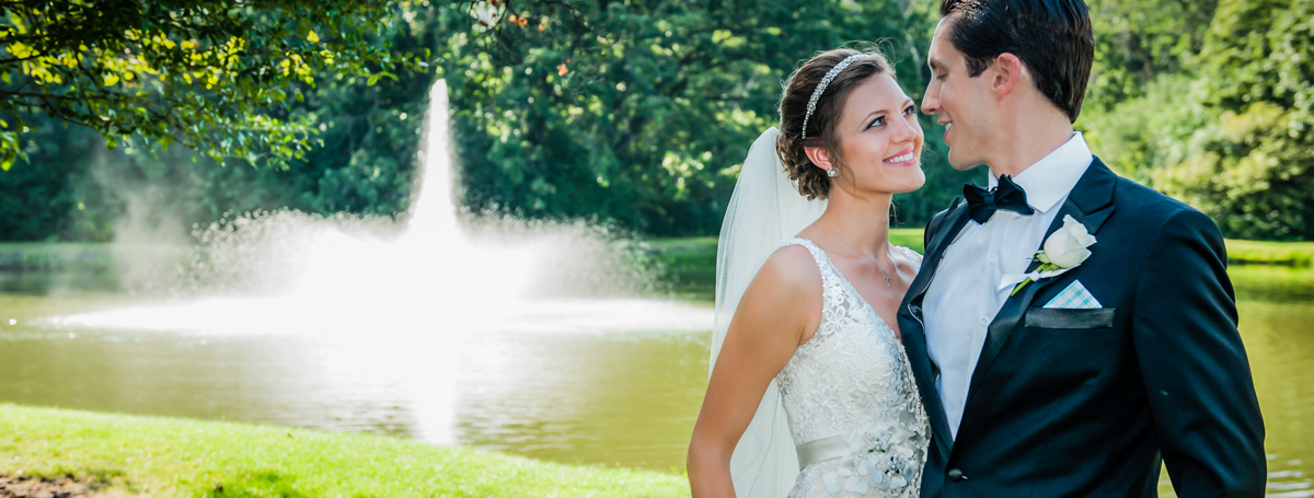 Bride and Groom Standing in Front of Pond and Fountain